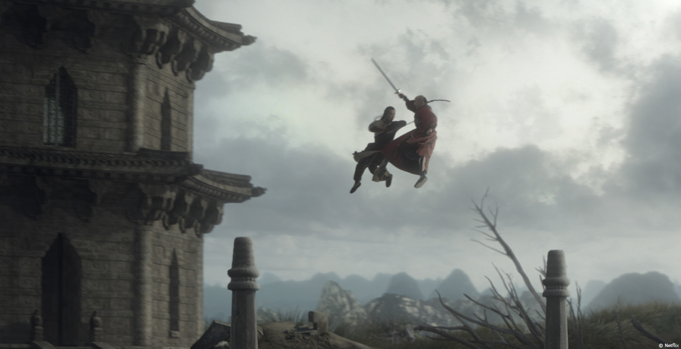 A still from a kung fu movie with two men in the air with swords