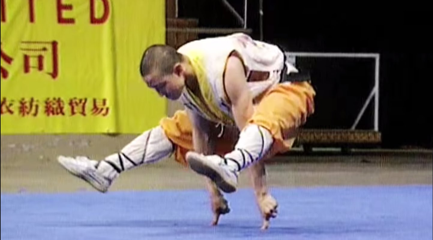 Shaolin monk balancing on pointer finger of each hand